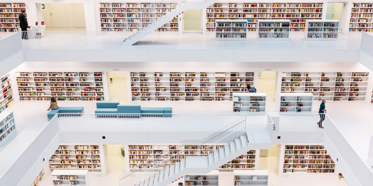 """""""Stuttgart, Germany - April 11, 2012: People walking along the bookshelves in the new public library of stuttgart, contemporary modern architecture public library."""""""
